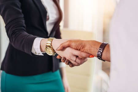 Photo for Female specialist shaking hands with a woman after successful job congratulating her - Royalty Free Image