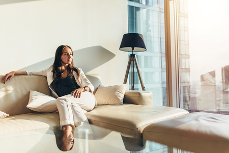 Photo for Portrait of successful businesswoman wearing elegant formal suit sitting on leather sofa relaxing after work at home - Royalty Free Image
