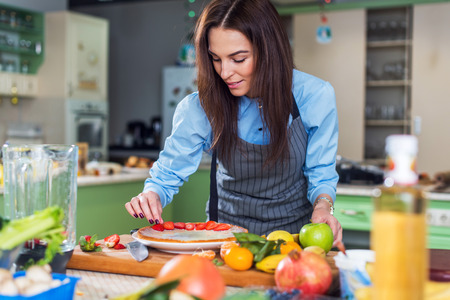 Photo for Pretty young woman smiling at camera while decorating a cake with sliced strawberry sitting in big kitchen - Royalty Free Image