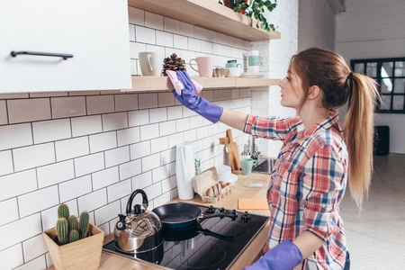 Photo for Woman in rubber gloves cleaning kitchen cabinet - Royalty Free Image