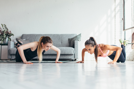 Photo for Two fitness women warming up doing push-ups exercise working out at home - Royalty Free Image