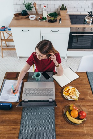 Foto de Young woman working with documents and laptop in the kitchen at home. - Imagen libre de derechos