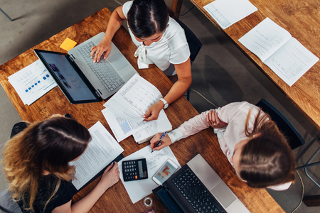 Foto de Team of female accountants preparing annual financial report working with papers using laptops sitting at desk in office - Imagen libre de derechos