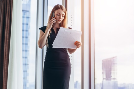 Photo pour Elegant young female business owner holding documents talking on mobile phone discussing contract conditions standing in office. - image libre de droit
