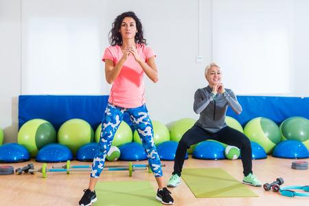 Foto de Two women in sportswear doing bodyweight squats while training indoors at sports hall - Imagen libre de derechos