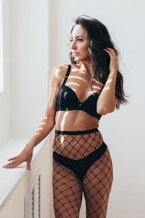Foto de Young sexy woman posing in black lingerie and pantyhose. - Imagen libre de derechos