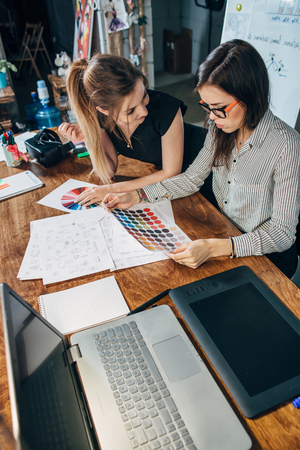 Photo for Young female graphic designers sitting at desk with laptop, color charts and some sketches discussing the new project choosing a concept - Royalty Free Image
