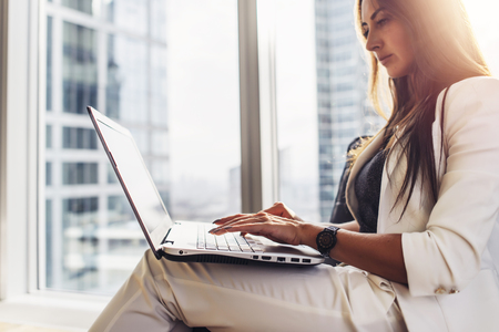 Photo for Young woman working on laptop sitting at home - Royalty Free Image