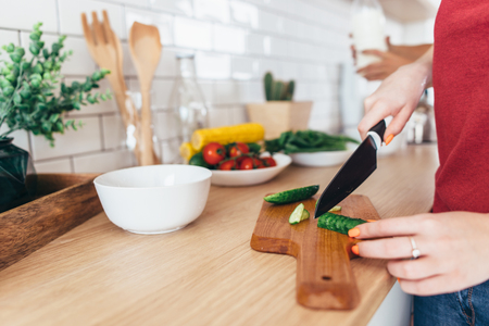 Foto per Woman cutting cucumber on the wooden board. - Immagine Royalty Free