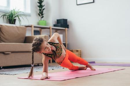 Foto de Little girl doing plank exercise at home. - Imagen libre de derechos