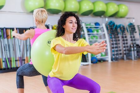 Photo pour Two young women doing squat exercises standing back to with a Swiss ball between them. Female athletes working-out in gym. - image libre de droit