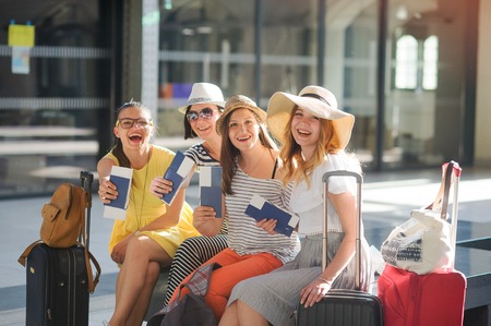 Foto per Charming tourists rejoice to the beginning of a travel. Girls sit at the station. They joyfully show the passports and tickets. Summer vacation. Anticipation of cheerful rest. - Immagine Royalty Free