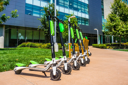 Foto de August 9, 2018 Mountain View / CA / USA - Lime Scooters lined up at the LimeHub in the Samsung campus in Silicon Valley, south San Francisco bay area - Imagen libre de derechos