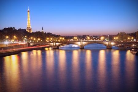 Foto de Paris, France - October 23 2011: Seine River and Eiffel Tower at dusk. The Eiffel tower is the most visited monument of France. - Imagen libre de derechos