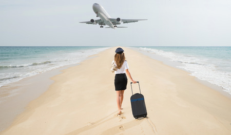 Foto de Travel concept. Young woman in flight attendant clothes walking on the beach with suitcase and hat. Overhead fly plane. - Imagen libre de derechos