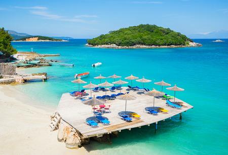Foto de Sunshade umbrellas and  deckchairs  on the beautiful Ksamil beach, Albania. - Imagen libre de derechos