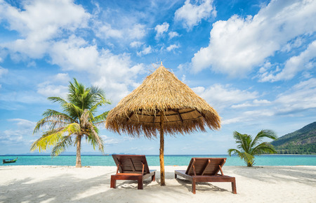 Photo for Vacation in tropical countries. Beach chairs, umbrella and palms on the beach.  - Royalty Free Image