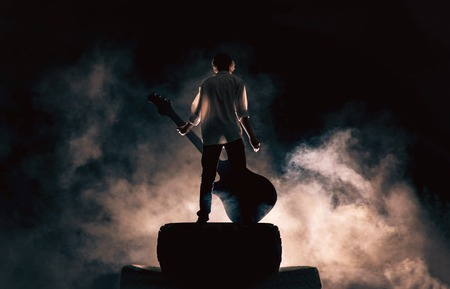 Photo for The musician plays on a large rock guitar in a great smoke - Royalty Free Image