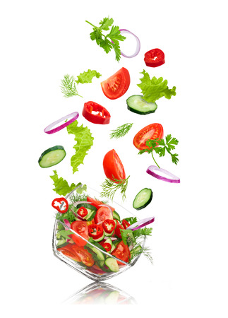 Photo pour glass salad bowl in flight with vegetables: tomato, pepper, cucumber, onion, dill and parsley. Isolated on white background - image libre de droit