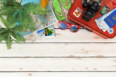 Foto de Travel concept. Sunbed, sunglasses, world map, beach shoes, sunscreen, passport, air tickets,camera, palms, beach ball, hat and old red suitcase for travel on the wood background. - Imagen libre de derechos