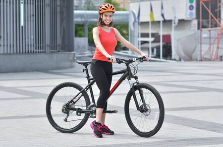 Foto per Girl wearing a tracksuit with helmet rides a bicycle through the streets. Summer day - Immagine Royalty Free