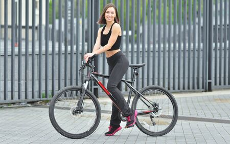 Foto per Young beautiful girl standing with her bicycle outdoor - Immagine Royalty Free