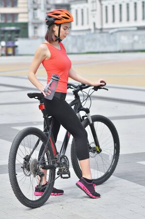 Foto per Fit girl is riding bikes through the streets of the city and smiling - Immagine Royalty Free