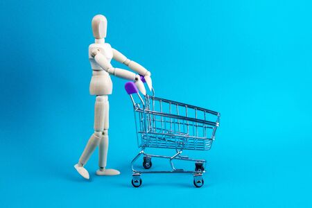 Shopping concept. Wooden doll and metal shopping cart.