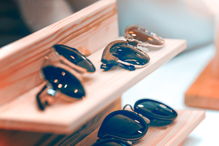 Photo pour Sunglasses on the shelf put in a row. The frame is made of metal and wood. The background is blurred. - image libre de droit