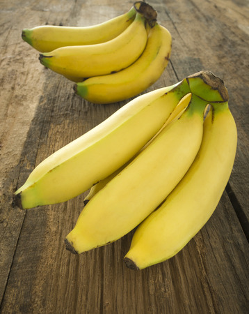 Photo pour Bunch of bananas ripe placed on a wooden table. - image libre de droit