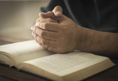 Photo pour Hands of a man in prayer on a Holy Bible . religion concept - image libre de droit