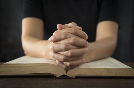 Photo pour Hands of a human in prayer on a Holy Bible . religion concept. - image libre de droit