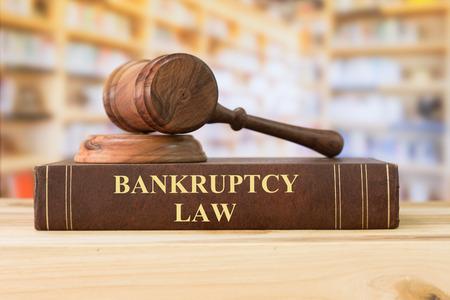 Foto de Bankruptcy Law books with a judges gavel on desk in the library. Concept of bankruptcy law,bankrupt,bankruptcy court,law education ,law books. - Imagen libre de derechos