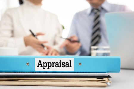 Foto de Appraisal documents on desk with manager and board are discuss about property appraisal or the appraisal process and performance ratings. - Imagen libre de derechos