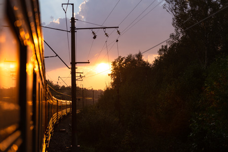 Foto per An electric locomotive. The train takes me into the sunset. Railway tracks curve. - Immagine Royalty Free