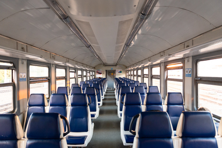Foto per An electric locomotive. An empty carriage. Rows of passenger seats. The last train. - Immagine Royalty Free