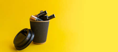 Foto de Kiev, Urkaine, 16 June 2020, Duracell AA alkaline batteries are in coffee takeaway cup as association of energy, yellow background, creative idea of using batteries. Enough space for text. - Imagen libre de derechos