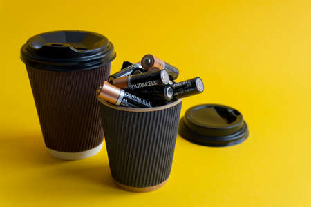 Foto de Kiev, Urkaine, 16 June 2020, Duracell AA batteries are in coffee takeaway cup with plastic lid and another cup with coffee to go,association of energy, yellow background,creative idea,space for text. - Imagen libre de derechos