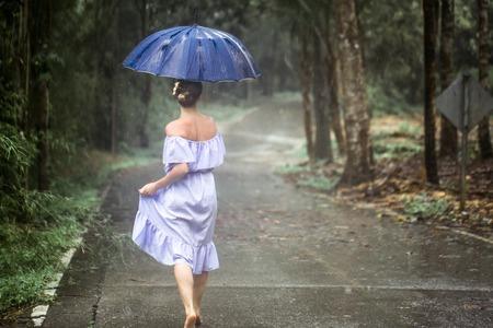 Beautiful young girl in dress with umbrella under the rain in the rain forest