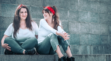 Foto de two girls in jeans and a white T-shirt, against the wall background, the concept of urban clothing, female friendship and youth style - Imagen libre de derechos
