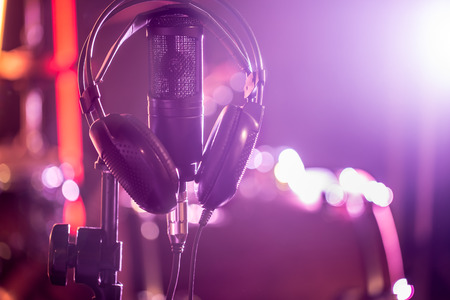 Photo for Studio microphone and headphones on a close-up stand, in a recording Studio or concert hall. Beautiful blurred background of colored lights. A musical concept. - Royalty Free Image