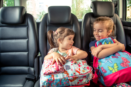Photo pour Children in the car go to school, happy, sweet faces of sisters, pupils of a kindergarten with school backpacks, sitting in the parental car - image libre de droit