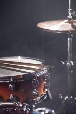 Photo pour Close-up Drum set in a dark room against the backdrop of the spotlight. Atmospheric background symbol of playing rock or jazz drums. Copper plates on a cold background - image libre de droit