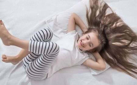 Foto de Cute little fun girl with long hair in bed woke up in the morning . Concept of sleep and development of children. - Imagen libre de derechos