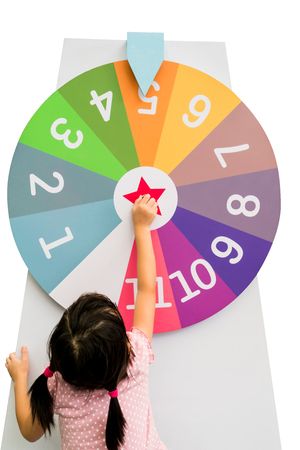Photo pour Asian girl trying to spin the huge colorful fortune wheel with white digit numbers isolated on white background - image libre de droit