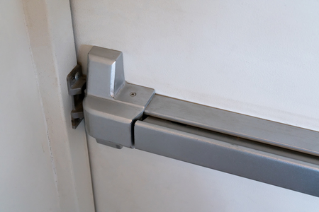 Foto de Closed up latch and door handle of emergency exit. Push bar and rail for panic exit. - Imagen libre de derechos