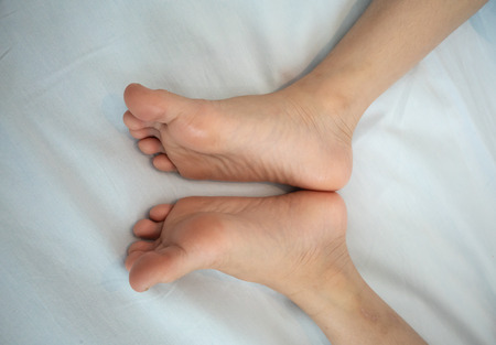 Photo pour Children's bare feet. Child's bare feet on white fabric background - image libre de droit