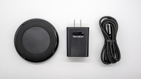 Foto de Black round shape wireless charger and adapter isolated on white background. - Imagen libre de derechos