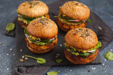 Photo for Healthy baked sweet potato burger with whole grain bun, guacamole, vegan mayonnaise and vegetables on a black board. Vegetarian food concept, dark foodphoto. - Royalty Free Image