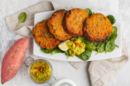 Photo for Homemade vegan baked sweet potato burgers in a white dish with guacamole. Vegan Healthy Food Concept. Light background, top view. - Royalty Free Image